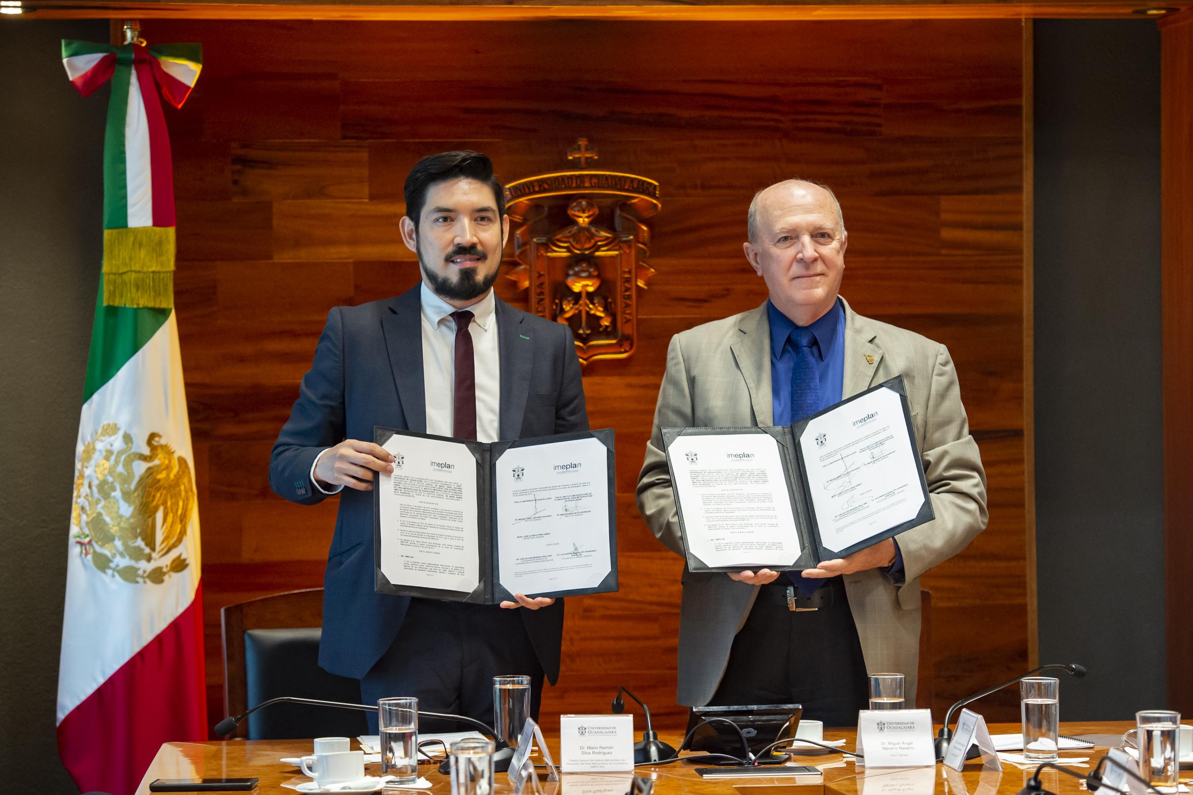 Rector General de la UdeG, doctor Miguel Ángel Navarro Navarro y el Director General del Imeplan, doctor Mario Ramón Silva Rodríguez, mostrando el convenio firmado