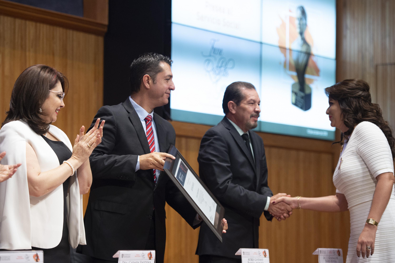 Esther Cisneros Quirarte recibiendo el reconocimiento de manos del maestro Gustavo Padilla Montes