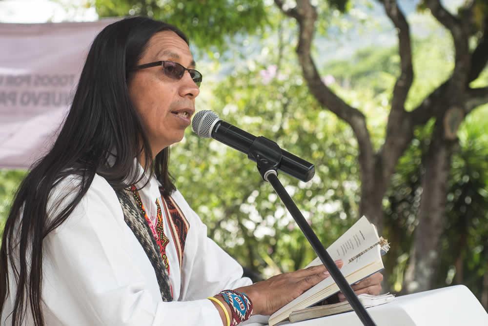 Persona con micrófono en podium instalado a las afueras de la naturaleza, dando lectura a un libro en su propia lengua indígena.