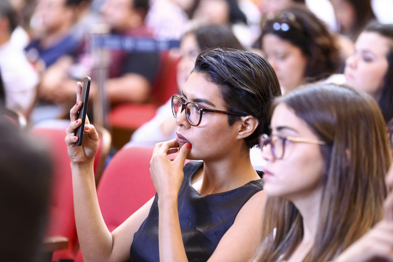 Estudiante de la Universidad de Guadalajara, tomando evidencia de la ceremonia con su dispositivo móvil.