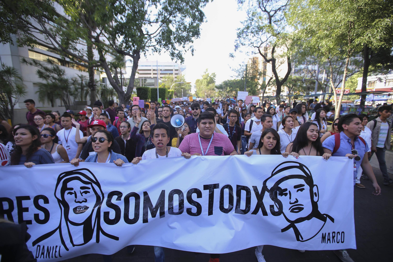 Manifestantes por la violencia y desapariciones que ocurren en Jalisco, con un cartel que dice -No somos tres, Somos todxs-.