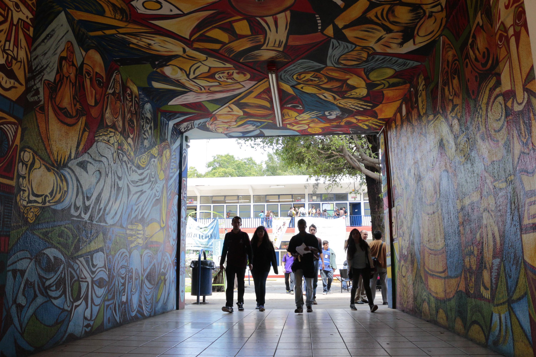 Alumnos de la Escuela Politécnica de Guadalajara, atravesando el pasillo con murales.