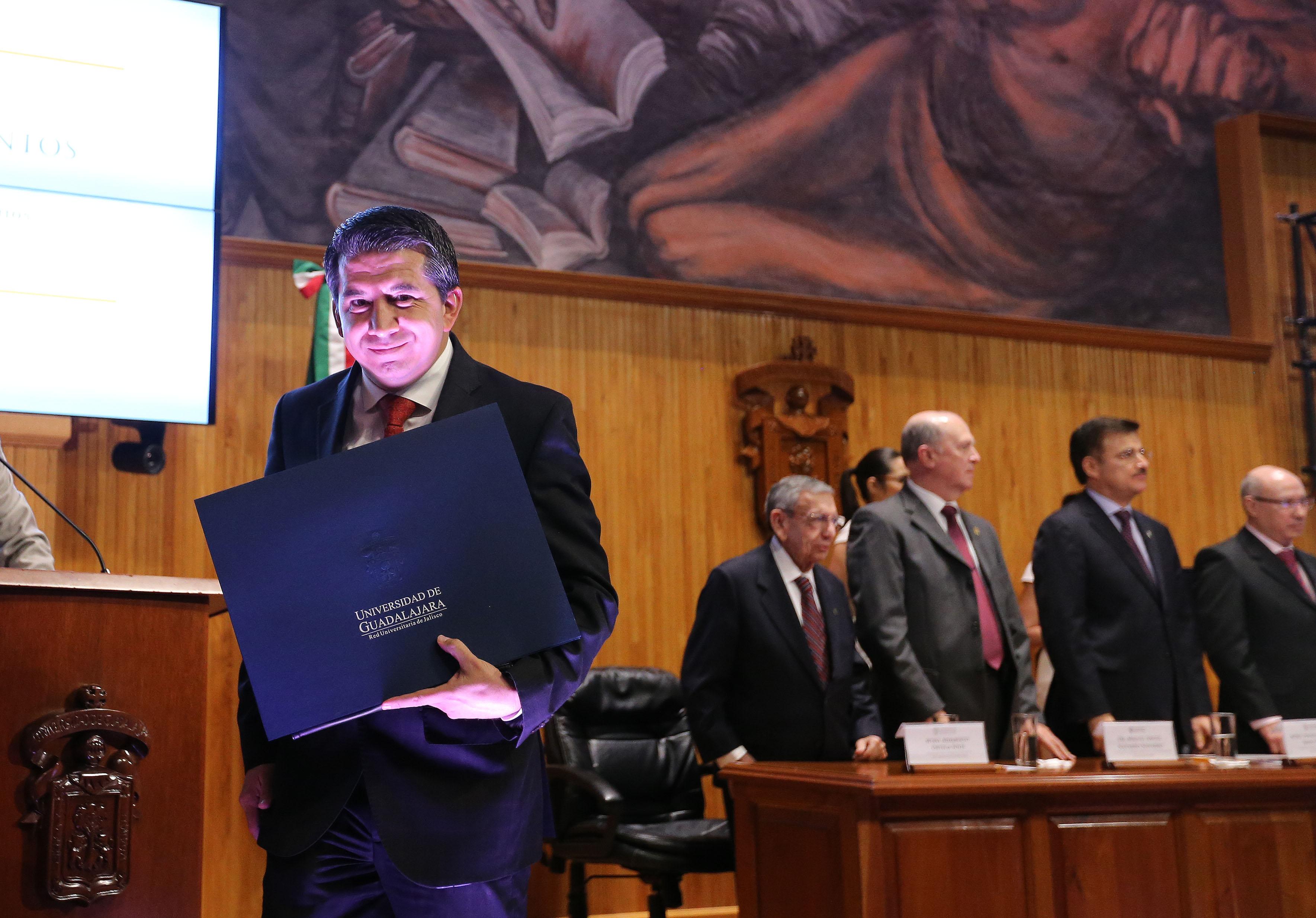 Maestro José Alberto Castellanos Gutiérrez, mostrando la carpeta de su  nombramiento, donde se le rectifico como Rectro del centro universitario de Ciencias Económico Administrativas (CUCEA).