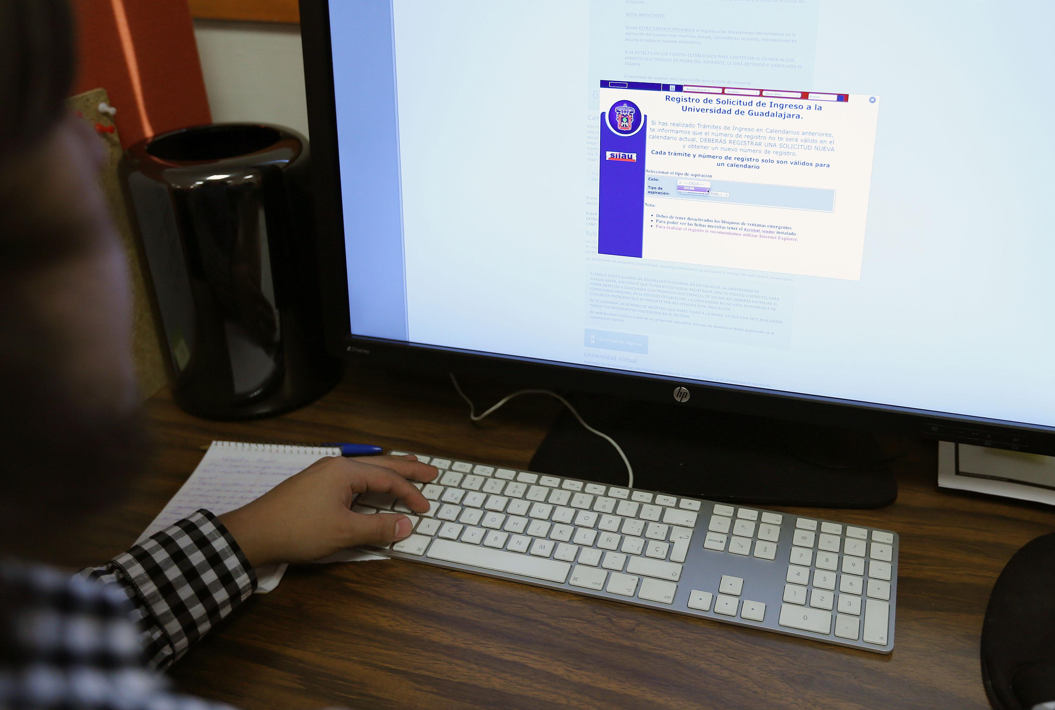 Alumno frente a monitor consultando la página electrónica para aspirantes a la Universidad de Guadalajara