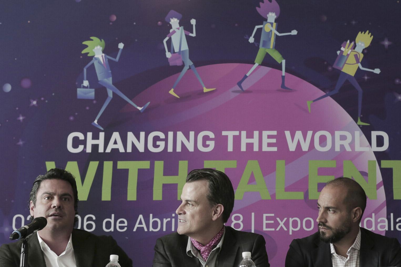 Detras de los presentadores hay una manta con la frase: Changing the world with Talent