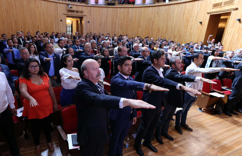 Todos los consejeros universitarios  extendiendo su brazo derecho durante la toma de protesta a su cargo