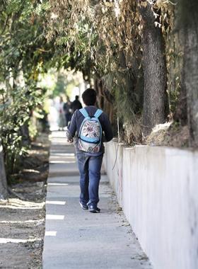 Estudiante caminando por la acera de una calle