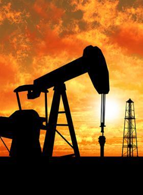 Puesta del sol deja ver sombra de Bomba de varilla extrallendo petroleo junto a varias torres petroleras