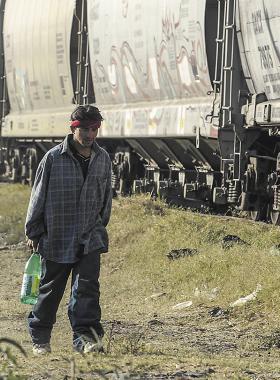Migrante caminando al lado de un tren
