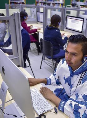 Estudiante indígena, dentro de laboratorio haciendo uso de computadora.