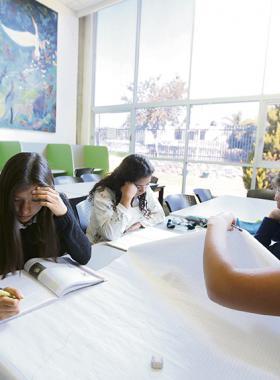 Grupo de mujeres de bachillerato estudiando.